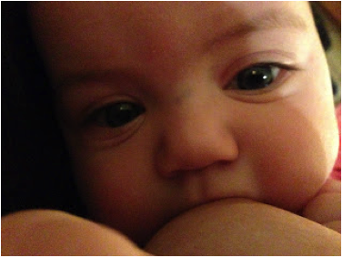 Close up face shot of a white infant with large green eyes latched onto her mother's breast