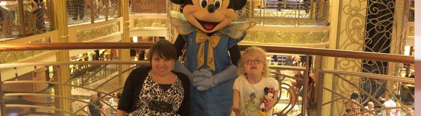 Photo of mother, a white woman and wheelchair user, and her daughter with Mickey Mouse.