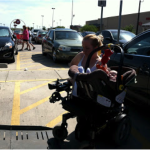photo of mother having unloaded baby from car with one arm