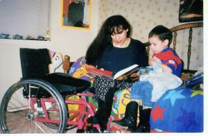 Woman sitting on bed reading book to young boy. Manual wheelchair is next to bed.