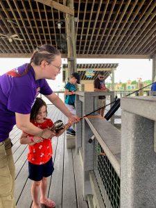 Morgan's Wonderland staff member helping 4 year old white girl hold a fishing rod.