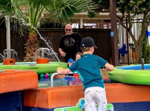 White man laughing as two small white children splashing in water tables