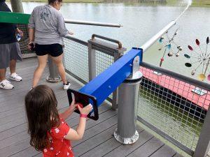 4-year-old white girl blasting giant water gun into pond.