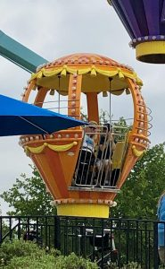 Orange pod of ferris wheel with woman in wheelchair and 7-year-old boy inside