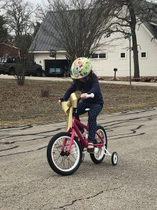Author's daughter on her bike with training wheels