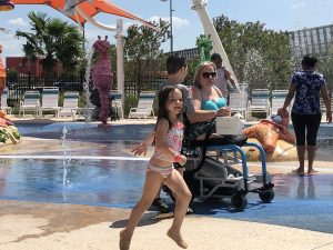 Color photograph of the author, a white blonde woman with only a right arm and no legs using a air powered wheelchair in the splash pad area with toddler daughter running beside her.