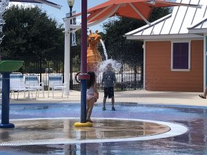 Color picture of the author's children playing at the waterpark. Author's school aged son is having water dumped on his head streaming out of the mouth of a seahorse statue. He is wearing black swim trunks and a gray rash guard with a skull and crossbones on it. Author's toddler daughter is looking on with her back to the camera, wearing a two-piece multicolored striped swimsuit.
