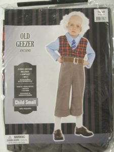 """Package costume for child in size small labeled as """"old geezer"""" features white school age child wearing a white wig, glasses, Miss matched clothing with pants pulled up nearly to his armpits and a significant gap between the bottom of the pants and his shoes revealing long white socks."""