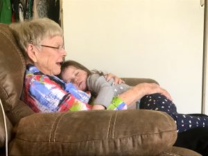 Color photograph of an elderly white woman sitting in a brown recliner holding a white toddler girl on her lap who is laying against her chest sleeping.