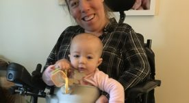 Photo of woman in wheelchair holding baby on her lap. Strap is around her and baby.