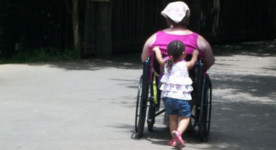 photo of little girl pushing woman in wheelchair