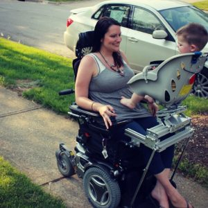 Mother in power wheelchair uses a specialized seat that attaches to her wheelchair. Son is able to sit facing her. Seat is from a bicycle.